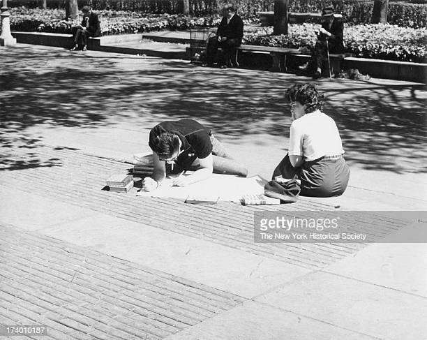 A man and woman sit in the sun with library books he is leaning over a map with a cigarette in his mouth Bryant Park New York New York August 25 1963