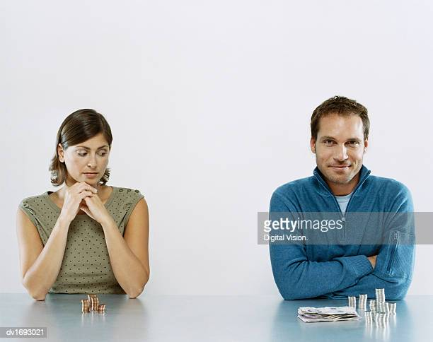 man and woman sit next to each other with a pile of money in front of them, woman looking jealous at man's pile - inequality stock photos and pictures