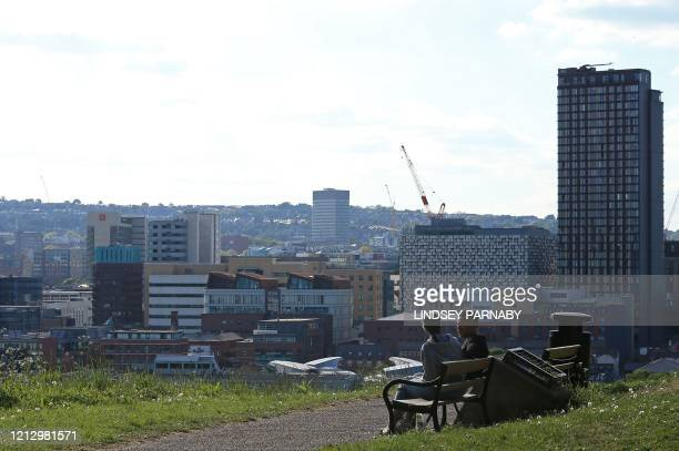 Man and woman sit on a bench and enjoy the sunshine in Norton Park, Sheffield, northern England, on May 14 following an easing of the novel...
