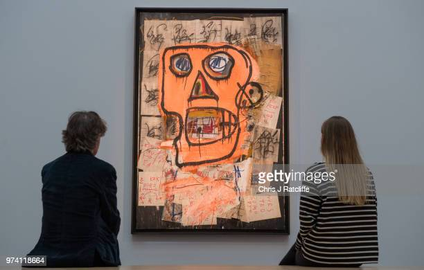A man and woman sit on a bench in front of 'Untitled' by JeanMichel Basquiat during a preview of the Contemporary Art sale at Sotheby's on June 14...