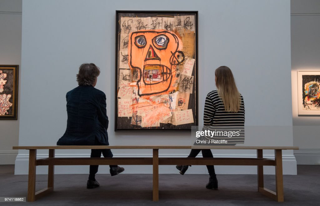 A man and woman sit on a bench in front of 'Untitled' by Jean-Michel Basquiat (estimated at £7.5 million to £10 million) during a preview of the Contemporary Art sale at Sotheby's on June 14, 2018 in London, England. The sale will take place on 26 June 2018 and includes works by artists Hockney, Freud and Basquiat.