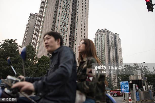 A man and woman sit on a scooter in front of the residential luxury homes of Guangcai in Beijing's Chaoyang district on September 29 2016 China's...