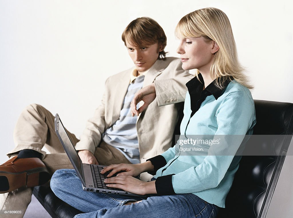 Man and Woman Sit Side by Side on a Sofa, Woman Using a Laptop : Stock Photo