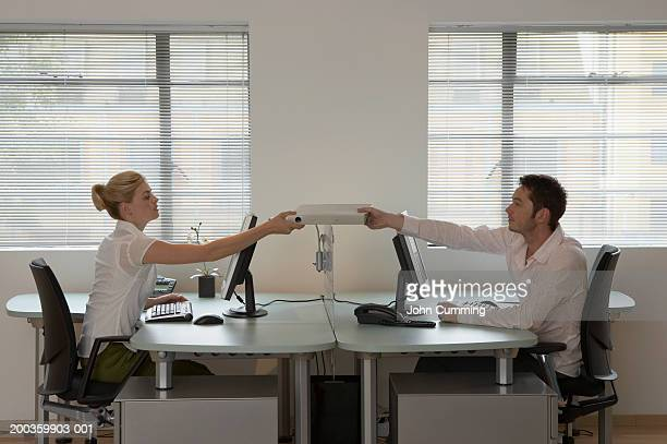 Man and woman sitting at opposite desks passing folder to each other