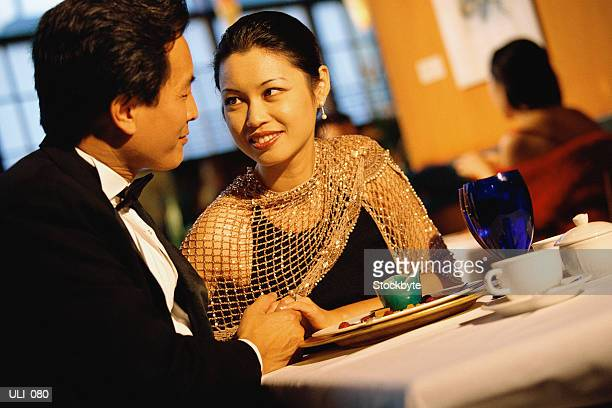 Man and woman sitting at restaurant table; man holding woman's hand