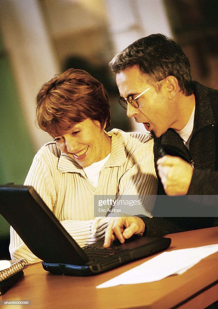 Man and woman sitting at table looking at laptop computer together. : Foto de stock