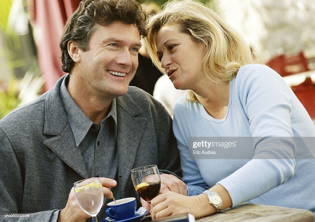 Man and woman sitting at table, woman whispering in man's ear,  close-up : Stockfoto