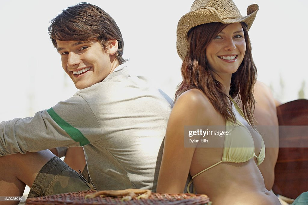 Man and Woman Sitting Back to Back : Stock Photo