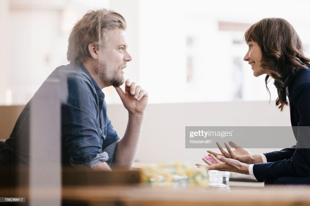 Man and woman sitting in cafe, discussing vividly : Stock-Foto