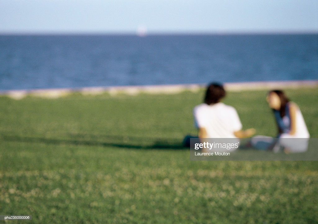 Man and woman sitting in grass by ocean, blurred. : Stockfoto