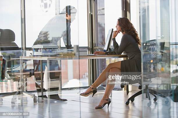 man and woman sitting in office, view from behind glass wall - flirting stock pictures, royalty-free photos & images
