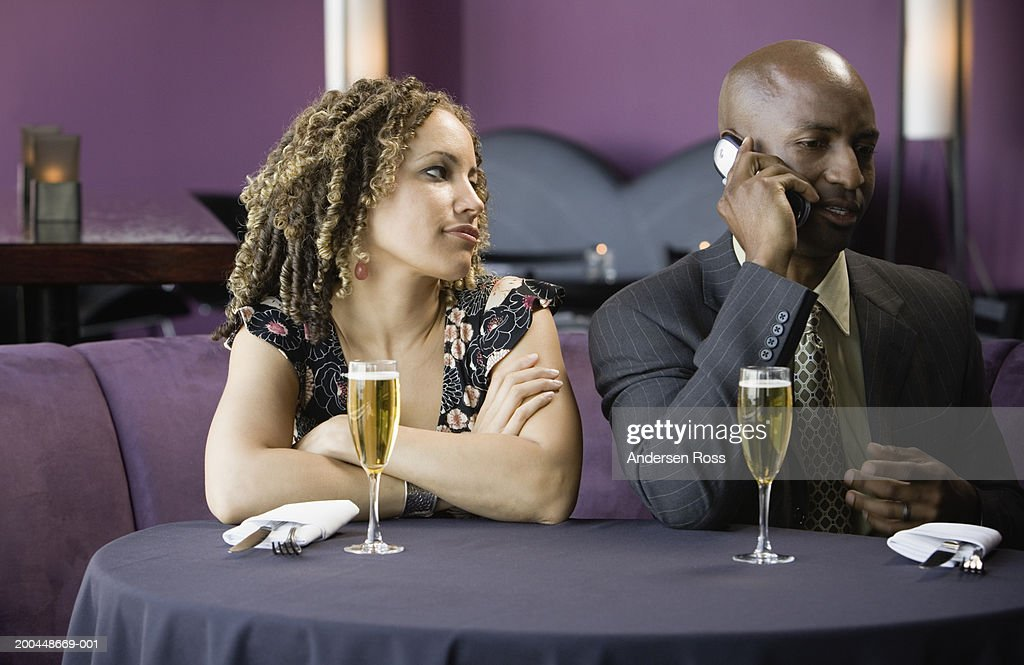 Man and woman sitting in restaurant, man talking on cell phone : Stock Photo