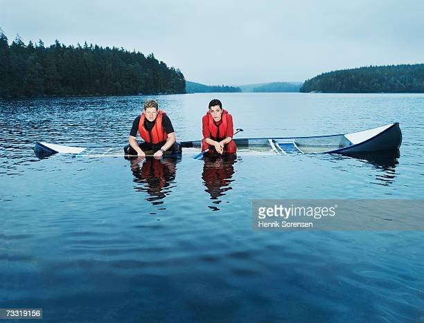 Man and woman sitting in sinking canoe