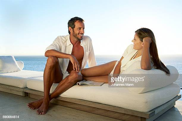 Man and woman sitting in sunlounger