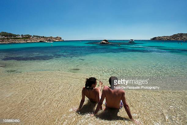 Man and woman sitting in surf, rear view