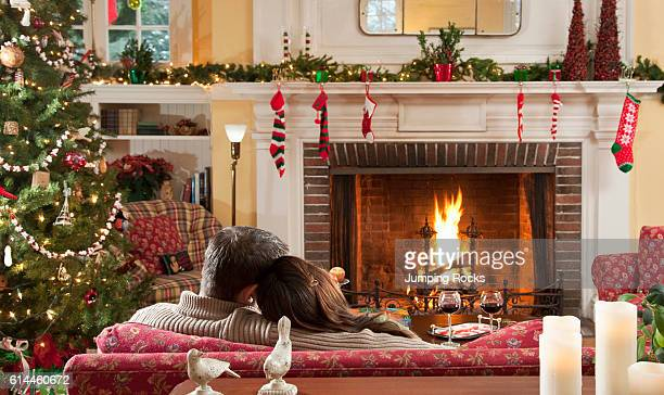 A man and woman sitting of sofa in front of lit fire