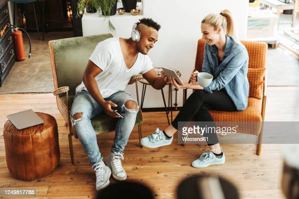 man and woman sitting on armchairs looking at digital tablet - seulement des adultes photos et images de collection