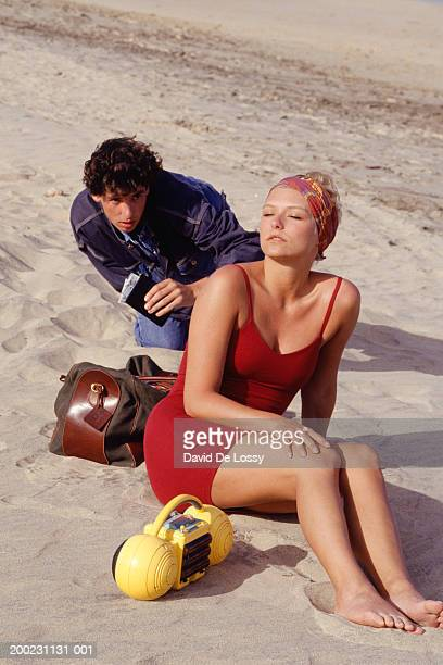 Man and woman sitting on beach, man lifting wallet from bag