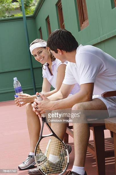 Man and woman sitting on bench by tennis court