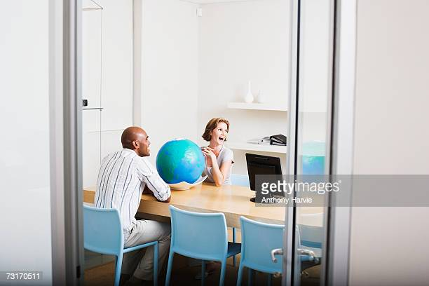 Man and woman sitting on chair with globe on desk, smiling