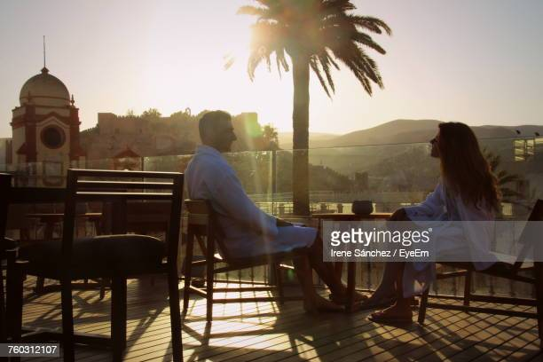 Man And Woman Sitting On Chairs At Resort