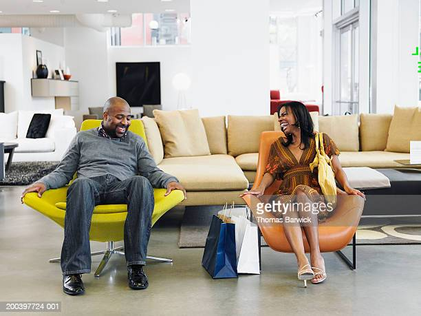 Man and woman sitting on chairs in retail furniture store, laughing