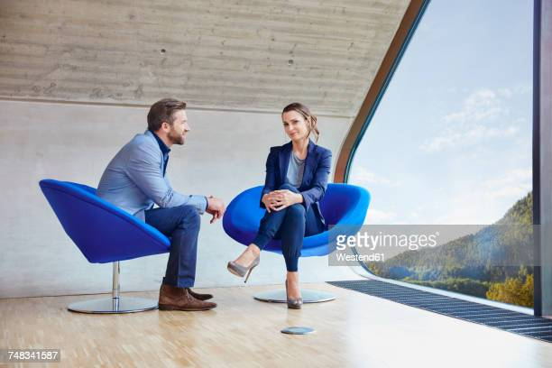 Man and woman sitting on chairs