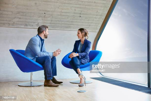 man and woman sitting on chairs talking - two people ストックフォトと画像