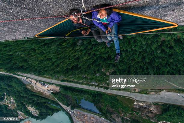 Man and woman sitting on hammock on bellygood ledge, The Chief, Squamish, Canada, overhead portrait
