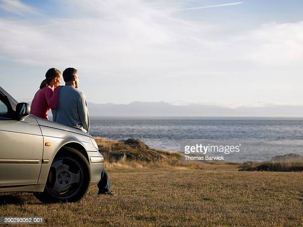 Man and woman sitting on hood of car overlooking sea, rear view