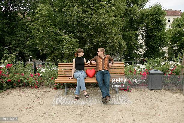 Man and woman sitting on park bench with heart pillow
