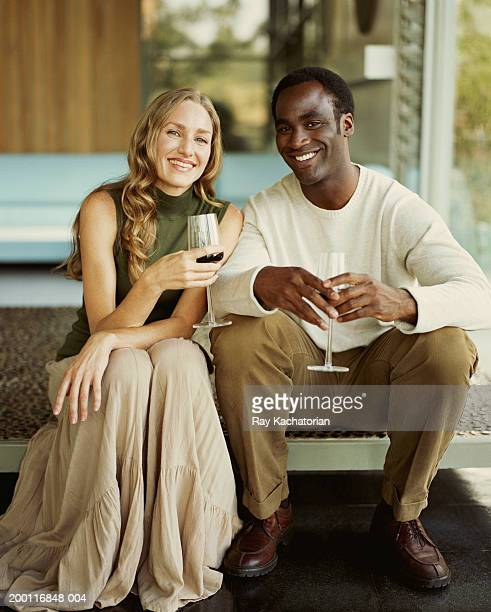 man and woman sitting on step, holding wine glasses - woman sitting on man's lap stock pictures, royalty-free photos & images