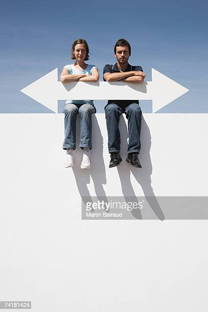 Man and woman sitting on wall outdoors with blank arrow