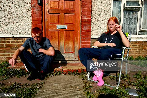 A man and woman sitting outside a house smoking