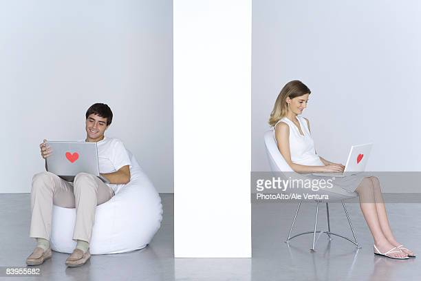 Man and woman sitting separately, using laptop computers with hearts on them, smiling