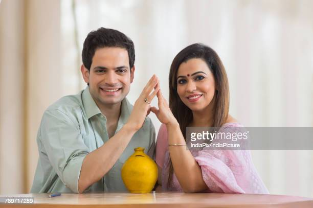 Man and woman sitting together on table with piggy bank