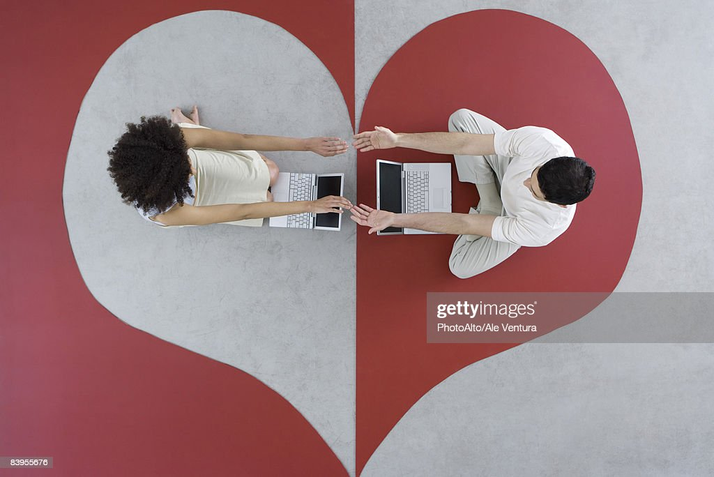 Man and woman sitting with laptops on large heart, arms out, touching hands, overhead view : Stock Photo