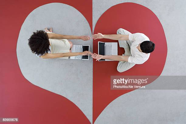 Man and woman sitting with laptops on large heart, arms out, touching hands, overhead view