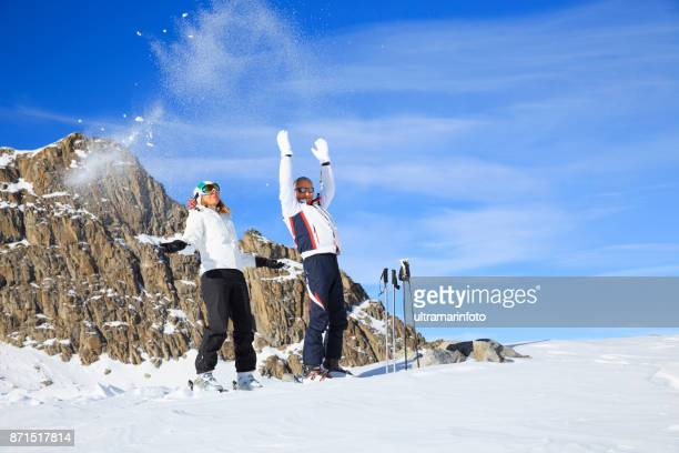 Man and woman skiers play with the snow at ski resort Dolomites in Italy
