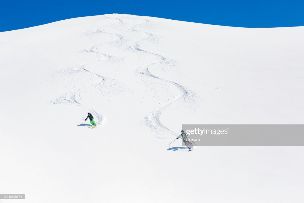 Man and woman skiing down mountain : Stock Photo