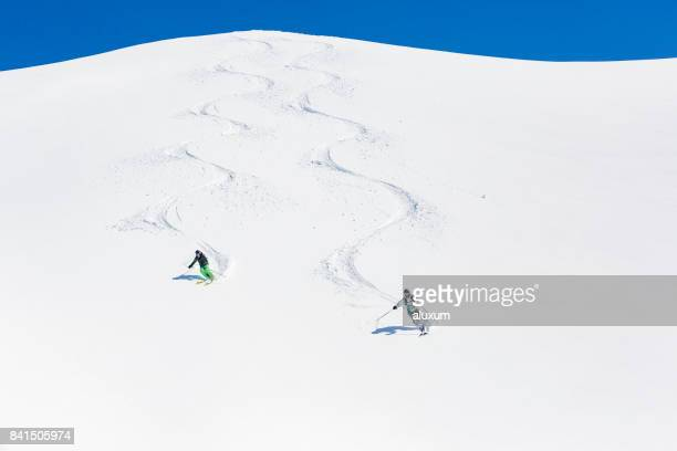 Man and woman skiing down mountain