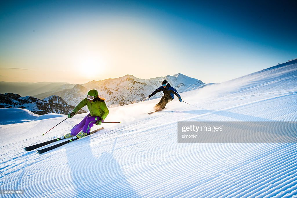 Man and woman skiing downhill : Stock Photo
