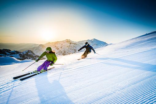 Man and woman skiing downhill 484707884