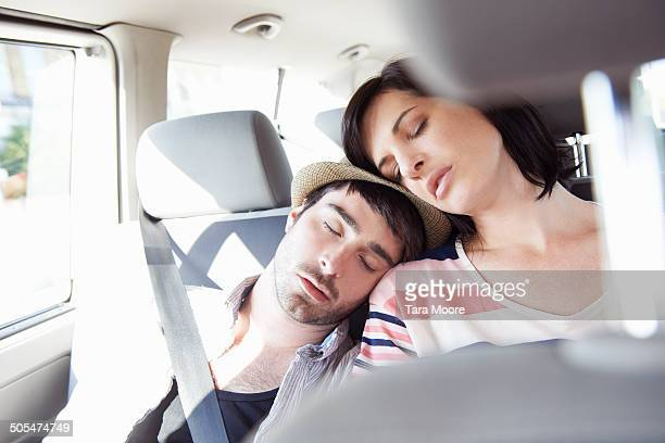 man and woman sleeping in car