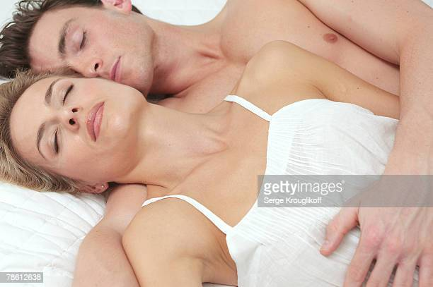 man and woman sleeping together - romantic young couple sleeping in bed stock photos and pictures