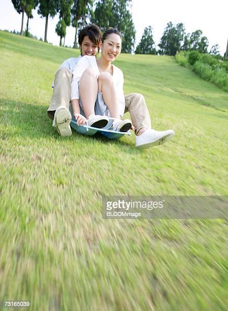 man and woman sliding downhill on grass - 滑る ストックフォトと画像