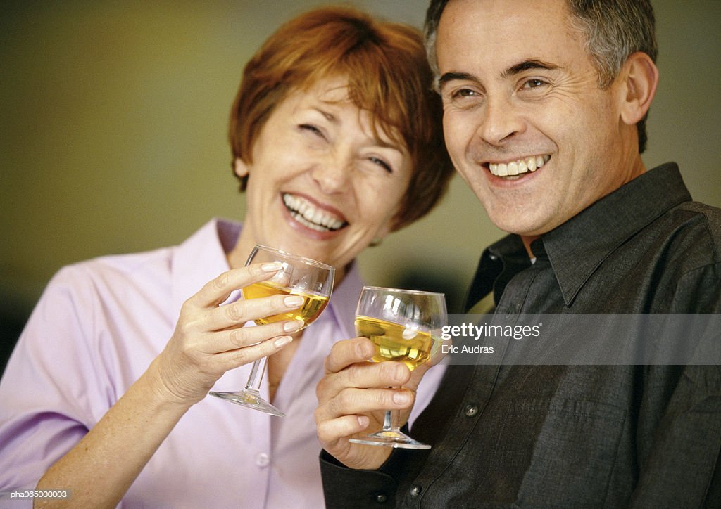 Man and woman smiling and holding up wine glasses, close up. : Stockfoto