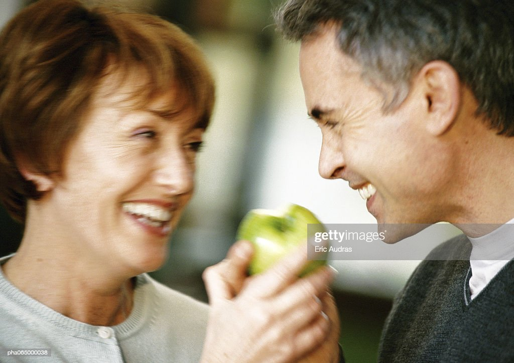 Man and woman smiling at each other, holding apple between them, close up, blurred : Stockfoto