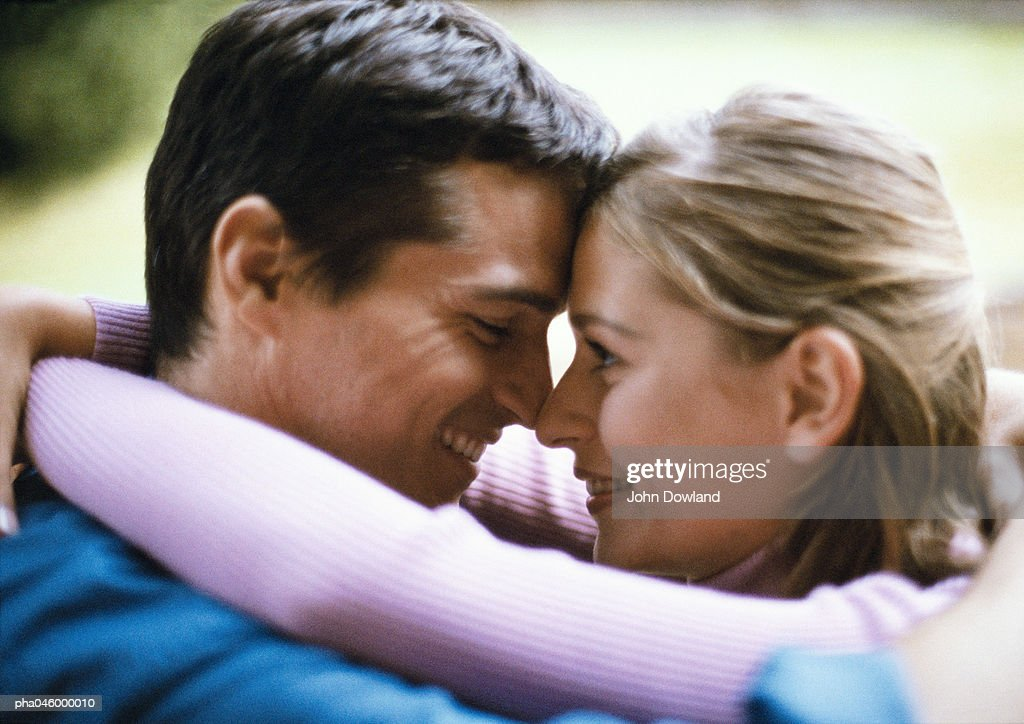 Man and woman smiling, foreheads and noses touching, side view, close-up : Stockfoto
