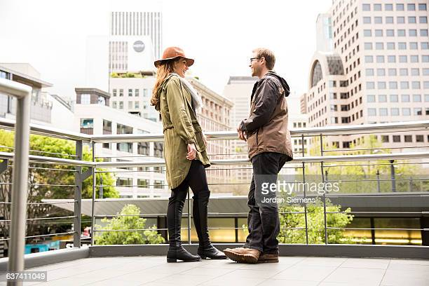 A man and woman smiling in the city.